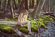 Full length of woman sitting on riverbank in forest - CAVF09730