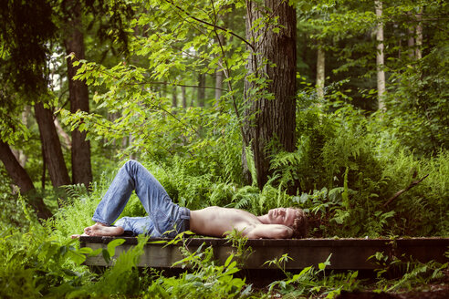 Shirtless man lying on pier in forest - CAVF09802