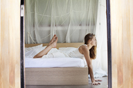 Side view of woman lying on bed at home - CAVF09829