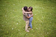 High angle view on man kissing girlfriend while embracing in field - CAVF09853