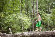 Side view of boy with fishing rod walking on fallen tree trunk in forest - CAVF09859