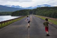 Rear view of boys skateboarding on road against sea - CAVF09877