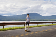 Boy looking down while standing on skateboard against cloudy sky - CAVF09880