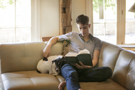 Man reading book while sitting with dog on sofa at home - CAVF09907
