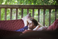 Thoughtful man relaxing on hammock by railing at home - CAVF09916