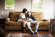 Couple holding coffee cups while sitting on sofa at home - CAVF09955