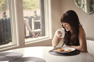 Happy woman by breakfast table at home - CAVF09958