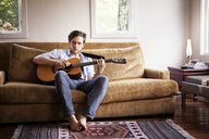Man playing guitar while sitting on sofa - CAVF09964