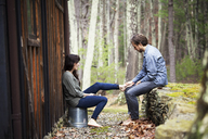 Side view of couple sitting by cottage - CAVF09976