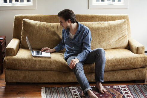 Man using laptop computer while sitting on sofa at home - CAVF09979