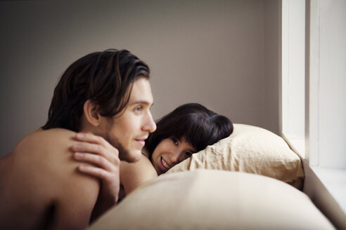 Man looking away while lying by girlfriend on bed at home - CAVF09982