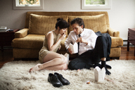 Couple eating food from carton while sitting on rug at home - CAVF10003