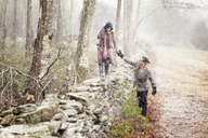 Man assisting woman walking on stone wall in winter - CAVF10060