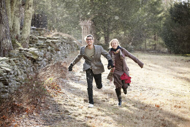 Happy couple running on field in forest during winter - CAVF10063
