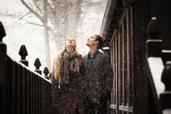 Couple looking up while standing by fence during winter - CAVF10081