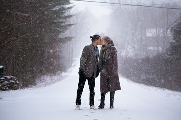 Romantic couple kissing while standing on snowy field during snowfall - CAVF10084