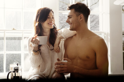 Happy couple holding coffee cups in kitchen at home - CAVF10126