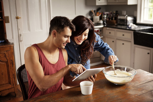 Man showing tablet computer to girlfriend in kitchen - CAVF10132