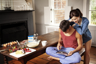 Couple searching recipe using tablet computer in kitchen at home - CAVF10135
