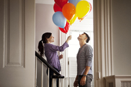Happy woman holding helium balloons while standing by man at home - CAVF10144