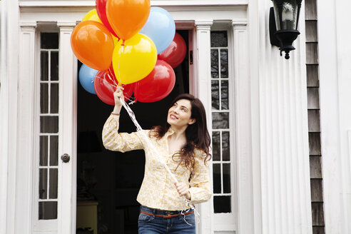 Woman holding helium balloons while standing outside house - CAVF10147