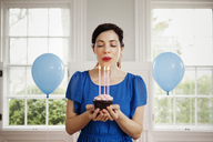 Woman holding cupcake with burning candles at home - CAVF10153