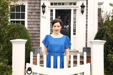 Portrait of woman standing by gate in backyard - CAVF10156