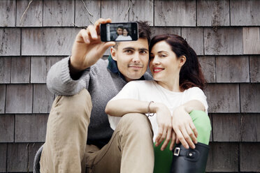 Man and woman taking selfie while sitting against wooden wall - CAVF10162