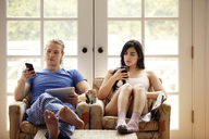 Couple using mobile phone while sitting on armchair at home - CAVF10183