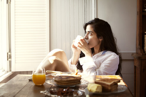 Thoughtful woman drinking coffee by breakfast table at home - CAVF10189