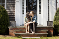 Couple kissing while on sitting steps at front stoop - CAVF10201
