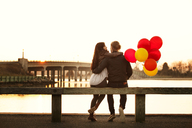 Rear view of couple with balloons sitting on railing during sunset - CAVF10216