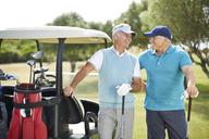 Senior men laughing next to golf cart - CAIF19547