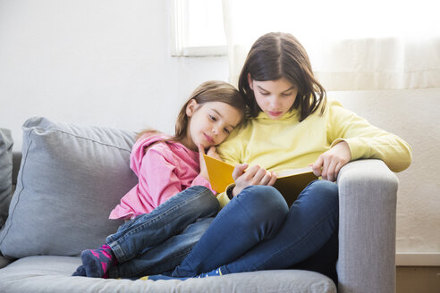 Two sisters sitting together on the couch reading a book - LVF06790