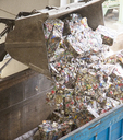 Bucket dumping recycled bundles into bin - CAIF19576