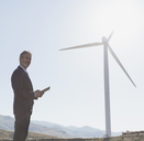 Businessman admiring wind turbine in rural landscape - CAIF19633