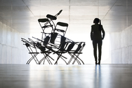 Businesswoman examining office chair installation art - CAIF19687