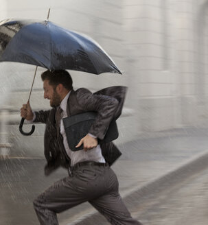Businessman with umbrella running in rain - CAIF19714