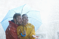 Happy couple under umbrella in rain - CAIF19726