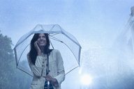 Businesswoman talking on cell phone under umbrella in rain - CAIF19729
