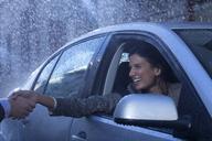 Smiling businesswoman in car extending handshake in rain - CAIF19762