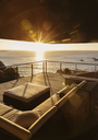 View of sunset over ocean from luxury balcony - CAIF19819