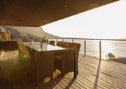 Dining table on luxury patio overlooking ocean - CAIF19855