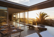 Patio overlooking swimming pool and ocean at sunset - CAIF19924