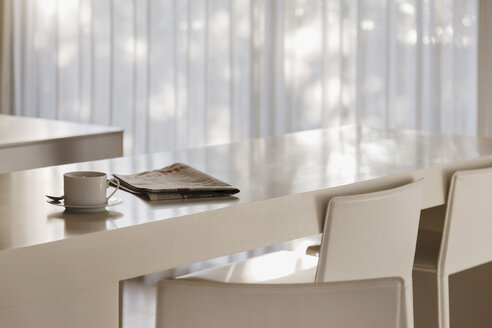 Coffee and newspaper on breakfast bar in modern kitchen - CAIF19930