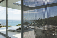View of ocean beyond patio and swimming pool - CAIF19936