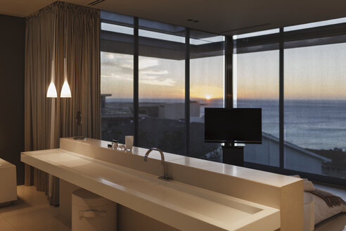 Modern sink in bedroom overlooking ocean at sunset - CAIF19951