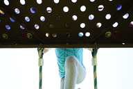Low angle view of girl peeking through hole while climbing rope ladder at playground - CAVF10372