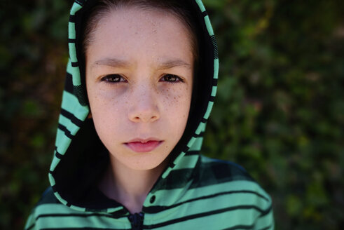 Portrait of confident boy in hood at park - CAVF10393