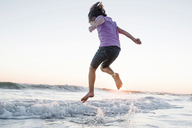 Low angle view of girl jumping on waves at beach against clear sky during sunset - CAVF10414